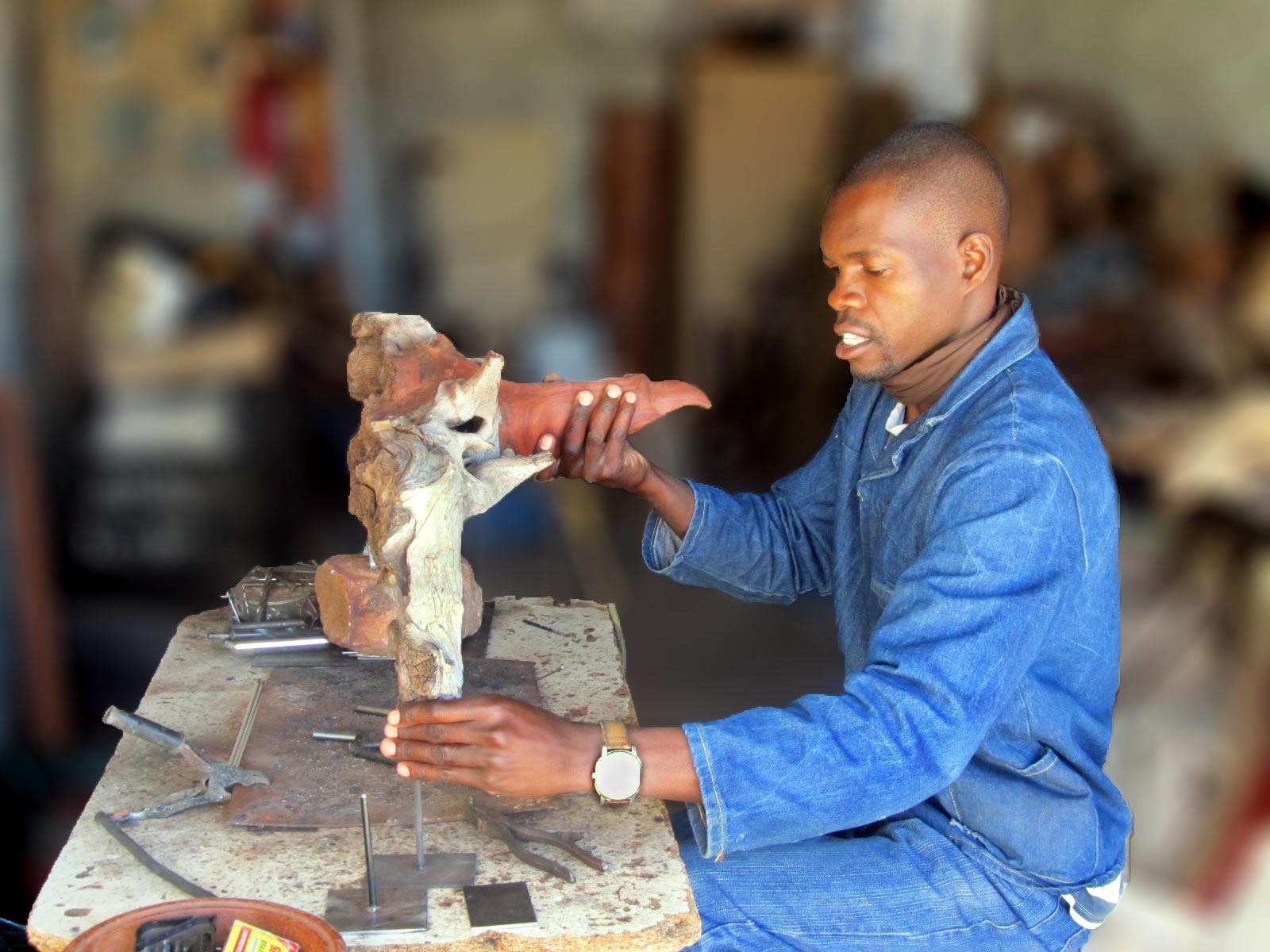 Boniface Chikwinhere creating wooden sculpture