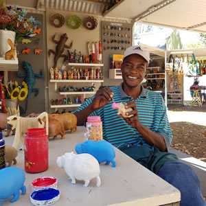 Hamilton Mbenuka with his carved and painted wooden animals